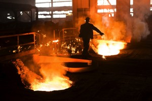 Worker next to smelting pits in steel mill